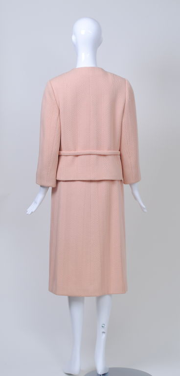 An exquisitely tailored suit in a pale pink, herringbone-patterned wool. An off-center closure with stitched outline continues in line from the jacket through the skirt. The one-button jacket, with an unusual spread collar and above-wrist sleeves,