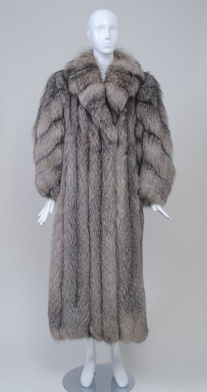 Luxurious silver fox maxi coat of high quality skins with beautiful natural coloration. The straight, slim body has vertical skins and a cross-cut shawl collar; the skins on the balloon sleeves are worked diagonally and the wrists are tapered. The