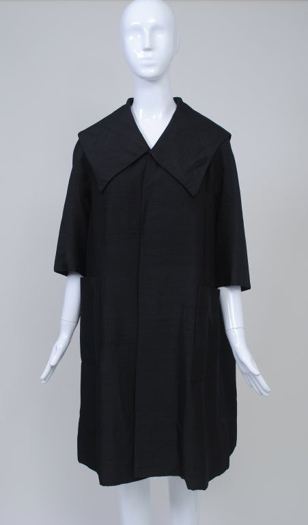 A vintage black opera coat is one of the most versatile items to have in your closet. This lightweight version has a casual vibe and can be worn daytime into night. Add a brooch for drama. Of raw silk and modified swing style, the coat features