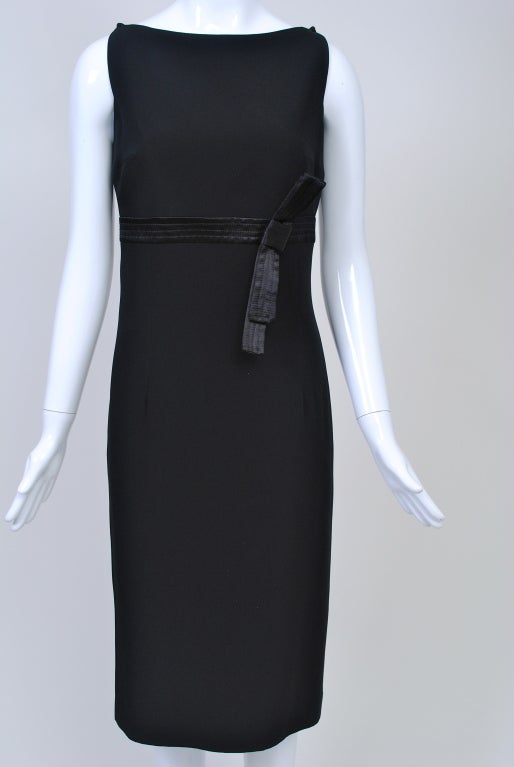 Great LBD by Gianfranco Ferre. Of black crepe, the fitted sleeveless sheath features an empire stitched satin band with bow, squared armholes and overlapping points at the shoulders. In back, the bottom of the skirt flares at the hem to relieve the