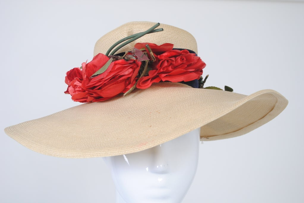 "Wide-brimmed natural straw hat w/wide navy velvet band and red fabric roses. Small high crown perches on top of head, does not pull down, lined in taffeta. Wide brim, 5 1/2 inches at front tapering to 4 "" in back, contains wire at edge for shaping."