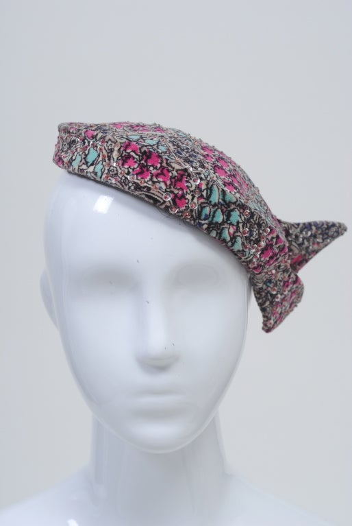 1950s hat in beautiful shades of aqua and rose printed velvet adorned with silver sequins. Perch it in different positions and secure with a hat pin. Labeled