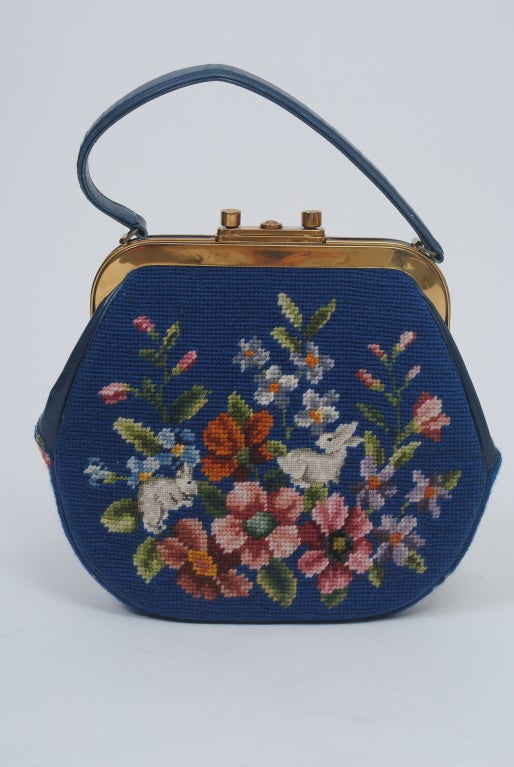 Tapestry and needlepoint handbags, so popular in the 1950s and '60s, are back in fashion. Here is a wonderful version from the 1960s in an unusual color, a beautiful medium blue, with matching leather trim. The floral needlepoint incorporates two