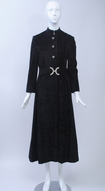"""Black crushed velvet evening coat features a Mandarin collar and separate 2"""" wide self belt with rhinestone buckle. Three domed rhinestone buttons in bound buttonholes and two interior snaps below. Side slit pockets. Petite in size and scale."""