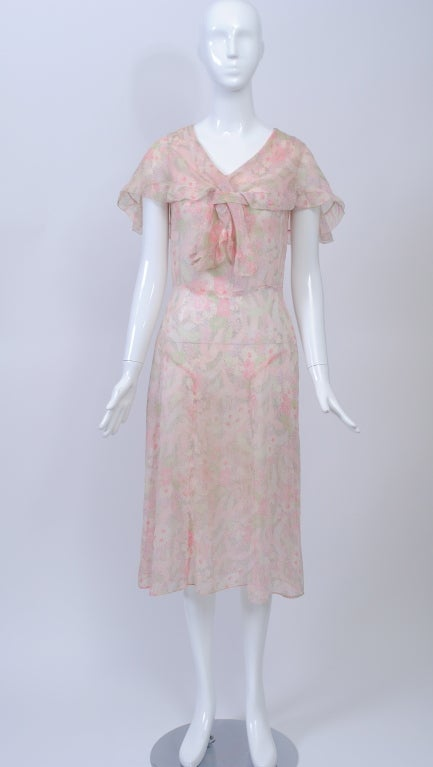 Floral voile 1930s day dress in pastel colors. Sleeveless bodice has capelet effect with ruffle border and ties that fit through tab. Paneled skirt flares at sides. Slips over the head. Add a picture hat and enter the world of Gatsby.