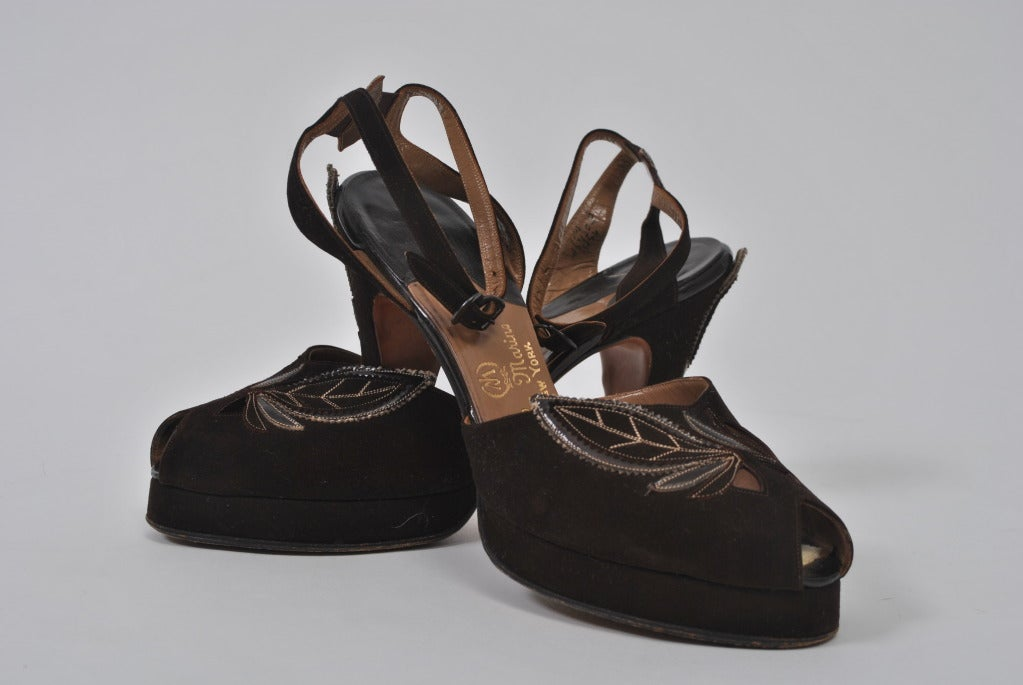 Hard-to-find 1940s brown suede platform shoes with brown leather leaf appliqués on instep and heel. Open toe and sandal back with ankle strap. In excellent condition. Heel measures 4