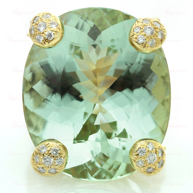 This fabulous ring from Christian Dior is made in 18k yellow gold and features a magnificient 23.0mm x 27.0mm oval light green faceted green aquamarine of an estimated 35 - 40 carats. The shank and the setting are beautifully accented with sparkling