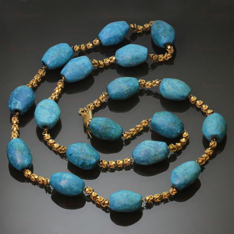 This fabulous vintage necklace features 15.0mm x 22.0mm pressed oval blue turquoise stones which have been treated for intensified color and set in a 32 inch 18k yellow gold chain of intricately textured links. Completed with a safety clasp. Vivid,