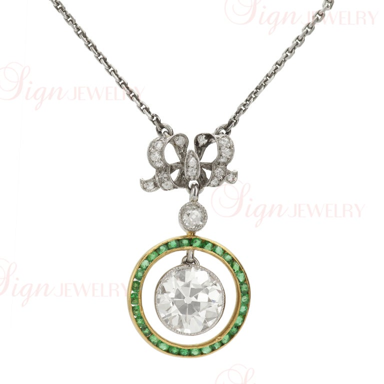 A beautiful and rare Belle Epoque pendant full of intricate features. A round diamond center stone (weighting approximately 2.05 - 2.25 carats) is suspended from a circular bezel-set and calibre-cut emerald crown which swings from a European-cut