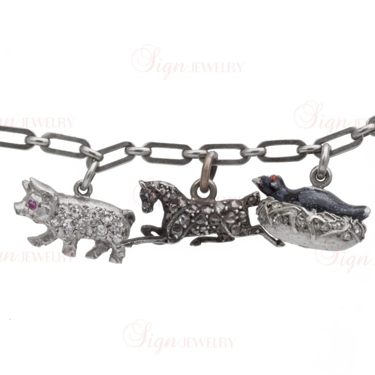 This antique hand-made link bracelet is crafted out of 9k white gold and features a total of 8 amazingly unique charms (two equestrians, a tank, a fox, a pig, a horse, a bird in a nest and letters VXKH). 7 charms are made of platinum while the horse