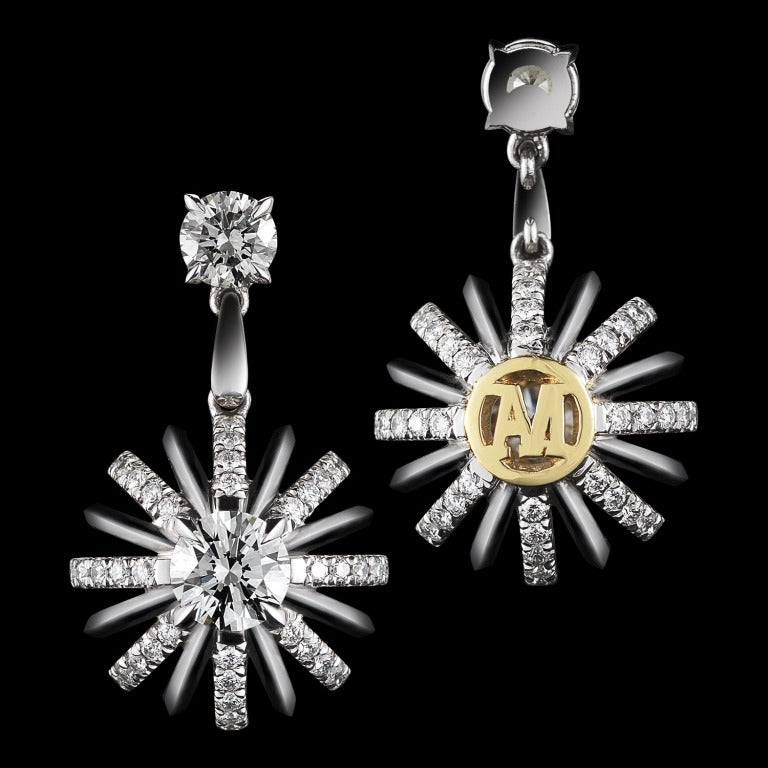 The Dangling Snowflake Diamond Earrings suspended by a pair of round Diamonds; featuring Alexandra Mor's signature details of 'floating' Diamond melee and knife-edged wire. Platinum set around 18-karat yellow gold AM logo gallery. Earrings measure