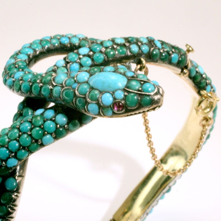 Elegant Victorian snake bangle bracelet with cabochon turquoise beads.  Designed as a coiled snake with large cabochon turquoise crowning the head.  Cabochon ruby eyes.<br />