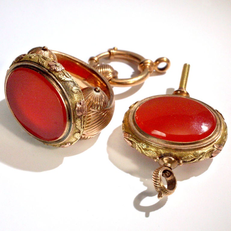 Striking antique watch fob set distinctly designed in a mixture of 14 karat yellow and rose gold.  The fob and the matching key with bezel cut vibrant colored carnelian stones.  Each piece with a ribbed pattern and delicate trailing flower design on