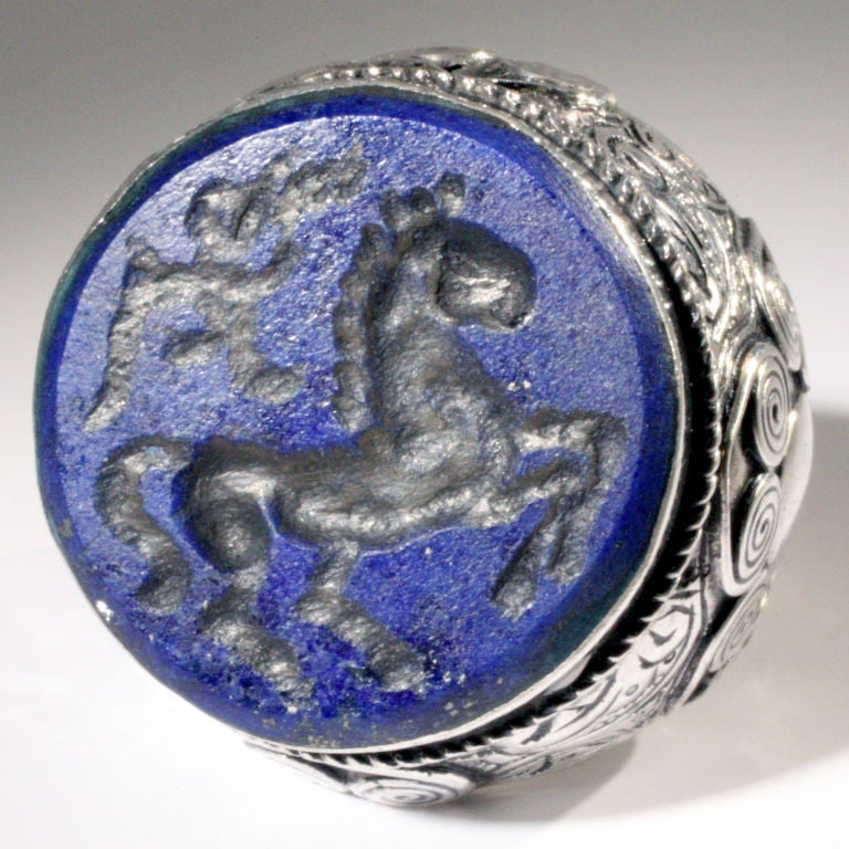 Large size embossed and engraved silver signet ring set with a blue lapis stone.   The stone with an intaglio of a galloping horse.  Size: 7