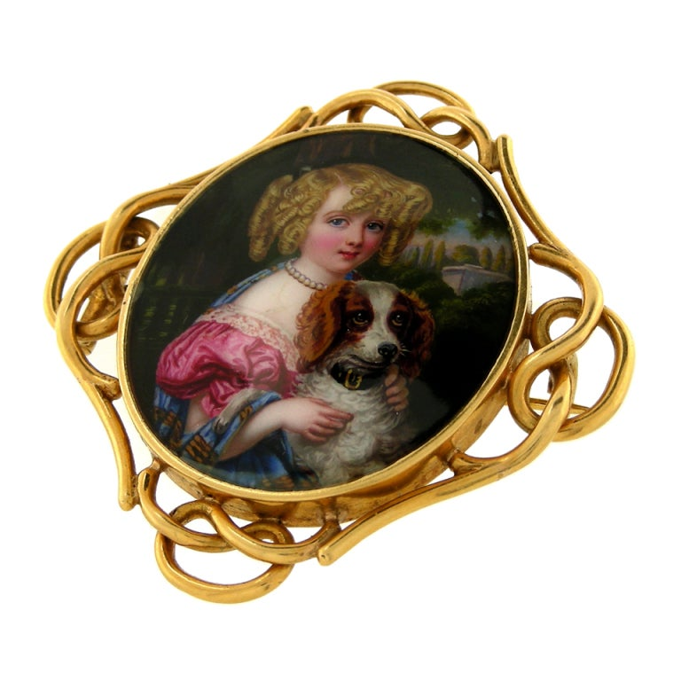 Utterly charming, this mid-Victorian brooch features a enameled portrait of a young girl with her dog. The enamel is exceedingly fine and bright with both the girl and dog well-figured. The costuming of the girl is particularly interesting and