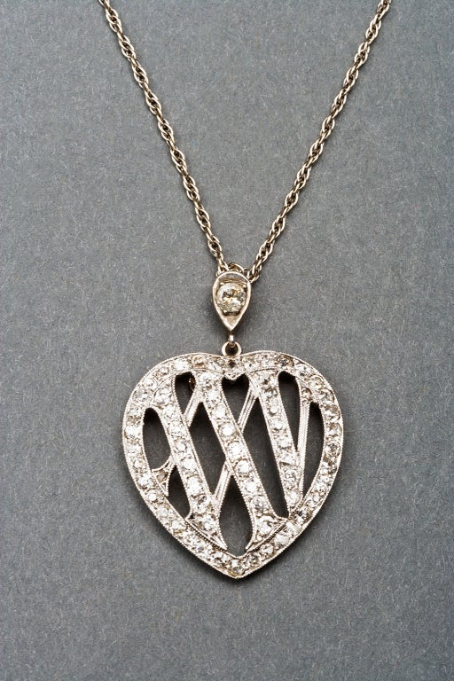 Heart-shaped, the openwork Roman numerals XXV set with antique-cut diamonds, suspended from a diamond set bail, mounted in platinum-topped gold, attached to a white gold chain.