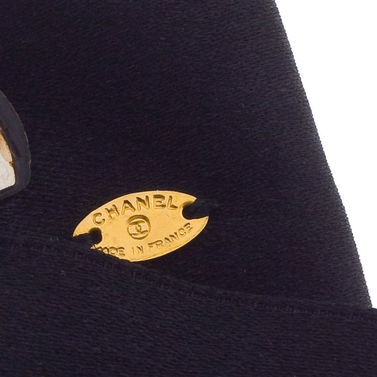 Very rare Chanel black bow hair barrette with gold toned CC logo motif.
