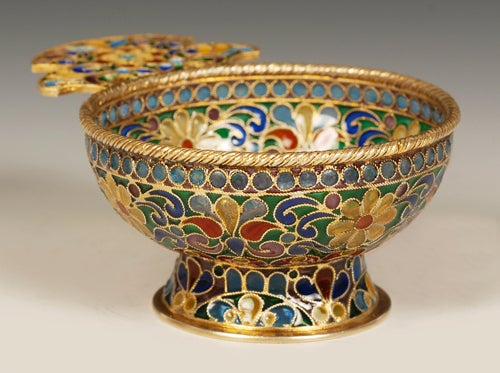 A Russian silver gilt and plique-à-jour enamel charka, no apparent maker's mark, Moscow, circa 1908-1917.  The entire body and shaped flat handled decorated with an intricate scrolling multi-color plique-à-jour enamel floral pattern against a gilt