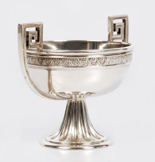 A Fabergé silver two-handled open salt, workmaster Alexander Wäkevä, Saint Petersburg, 1908-1917, with Fabergé scratched inventory number 21008. In Neoclassical taste, the round bowl with anthemia border and Greek key handles, raised on a flaring