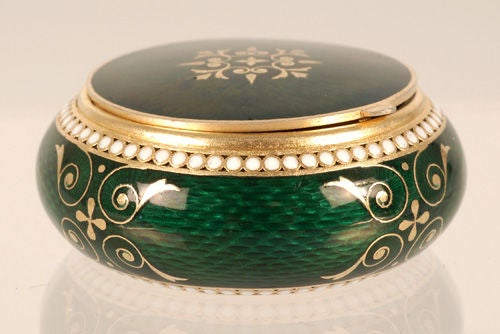 A Russian silver gilt and guilloche enamel box, Grachev Brothers, St. Petersburg, late 19th century. The circular box with bombe sides and hinged lid decorated in translucent emerald green enamel over a textured engine-turned ground with two bands