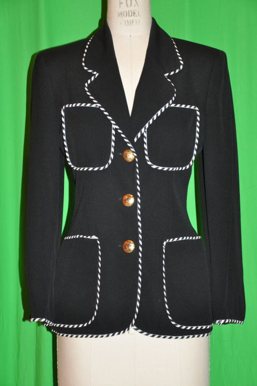 Moschino black with contrast candy-cane black? white piping detailing on edges, also on the front four (4) patch pockets. On front, there are three (3) gilded gold metal buttons with 'cheap & chic' detailing. The jacket is fully lined in