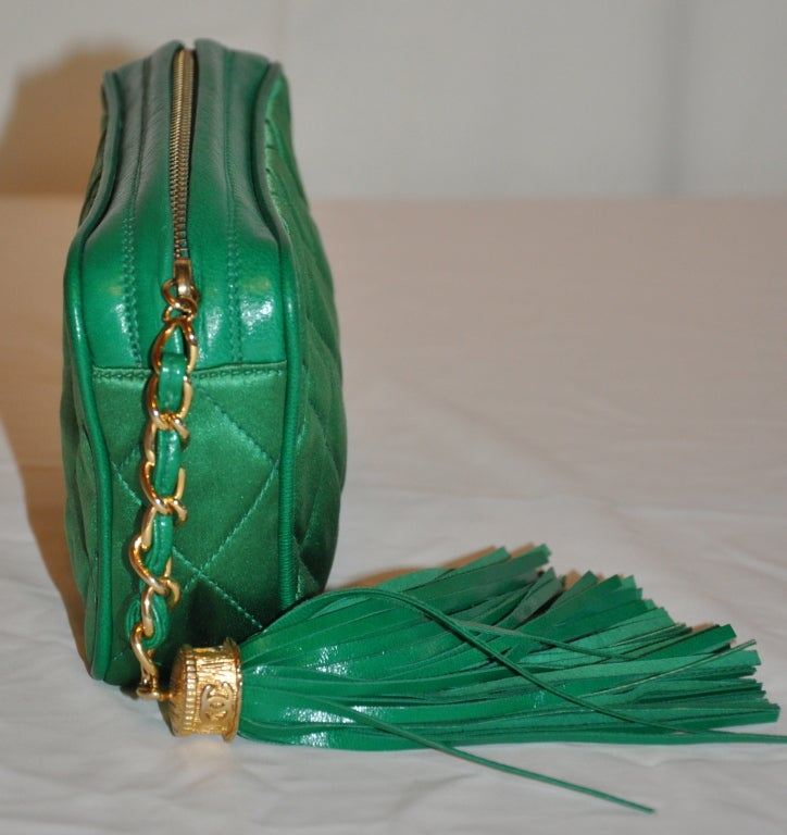 Chanel's rare quilted emerald-green silk-satin clutch has a zipper top and lambskin leather tassel with gold hardware. The edges are finished with lambskin leather piping. The interior is fully lined in lambskin.    The measurement are 3 3/4
