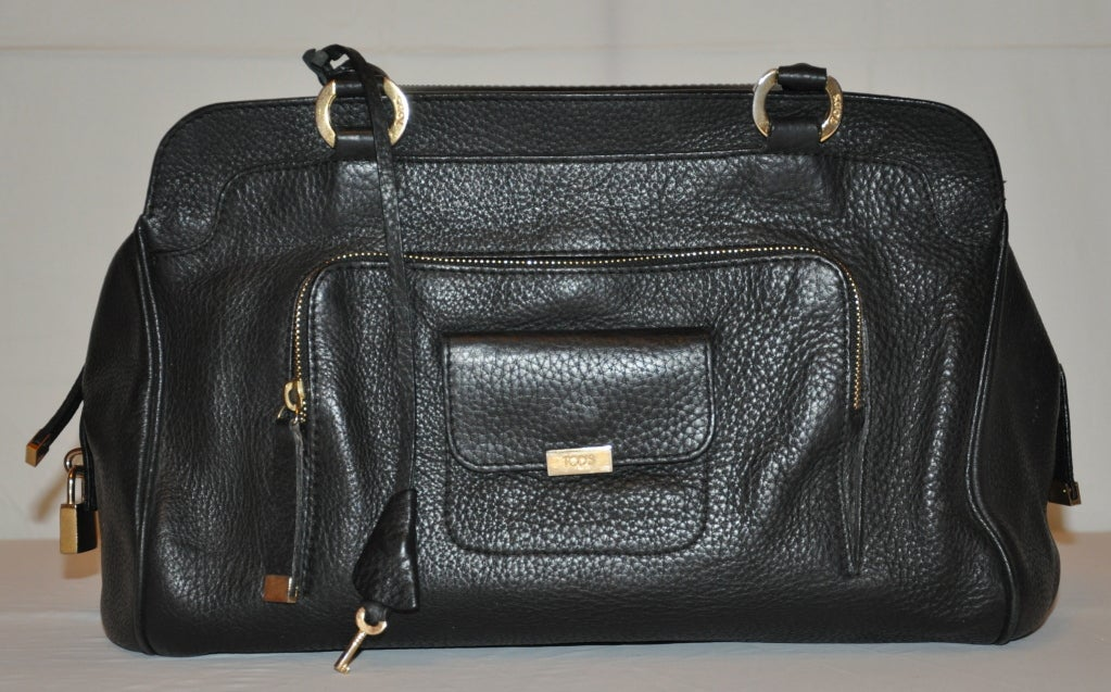 This wonderful Tod's handbag in black comes with a textured finished for less chances for scratches and better wear for everyday.    The exterior has two small compartments on front. One with a zippered top, and on top of it, another smaller