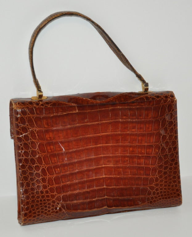 This wonderful golden brown Alligator-Skin handbag has three separate sections. The center one has a zippered compartment, while another has a opened compartment and the last, has a flap-over compartment. The front of the bag has a double