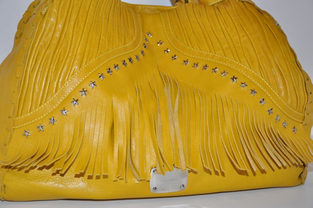 Jimmy Choo's Huge Banana-Yellow tote bag is accented with fringes and detailed with carefully folded lambskin on front along with embellished stars in gold hardware. Top-stitching is detailed throughout, as well as the hand-weave leather. 