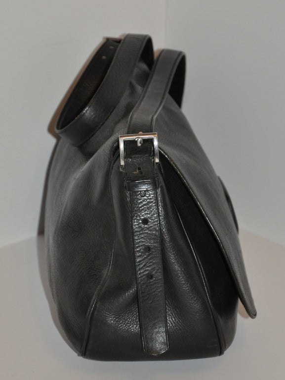 This Prada black textured shoulder bag has a flap including a buckle located at the bottom for added security. The straps can be adjusted if desire. Straps measures 58