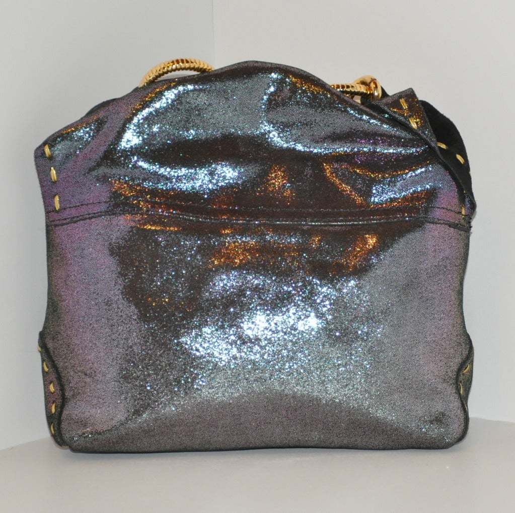 Carlos Falchi Textured gun-metal embossed calfskin are in hues of charcoal and plum with metallic gold threading hand-sewn throughout the bag. Accented with a heavy gold hardware chain handle and gold hardware pin on the flap. Interior has a