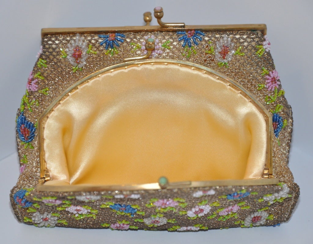 Brooks multicolored double-purse has micro-sized seed beading throughout. Hand-beaded in France, patterned with multi-colors of florals. Both purses are attached and fully lined with golden silk-satin. Both opening clasps are accented with