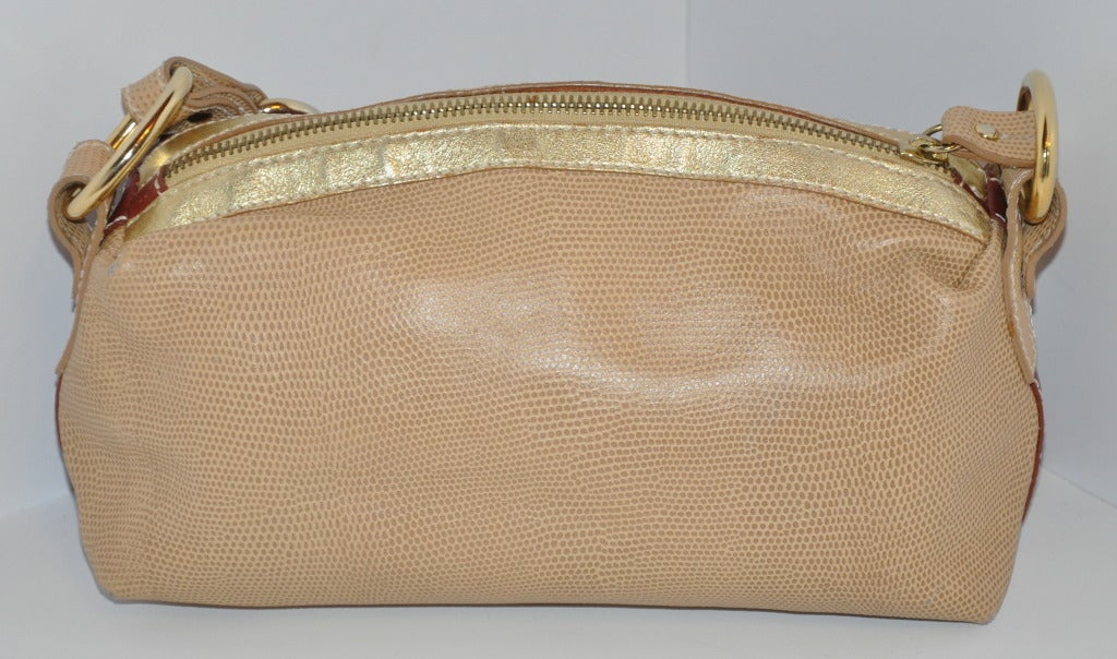 Dolce & Gabbana multi-textured calfskin bag has a combination of textured embossed snakeskin, metallic gold calfskin and top-stitched calfskin. The handles are with gold hardware and embossed snakeskin. Zippered opening on top with an embossed