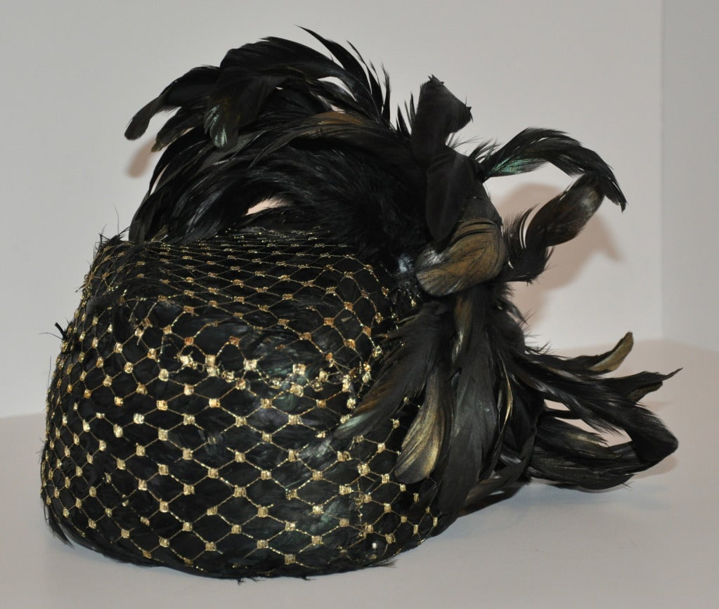 """Kokin's feathered hat is completely covered with deep iridescence green feathers covered with gold lame netting. Then, a full burst of feathers as a side crown! Diameter measures 23"""" and lined with wool-felt."""