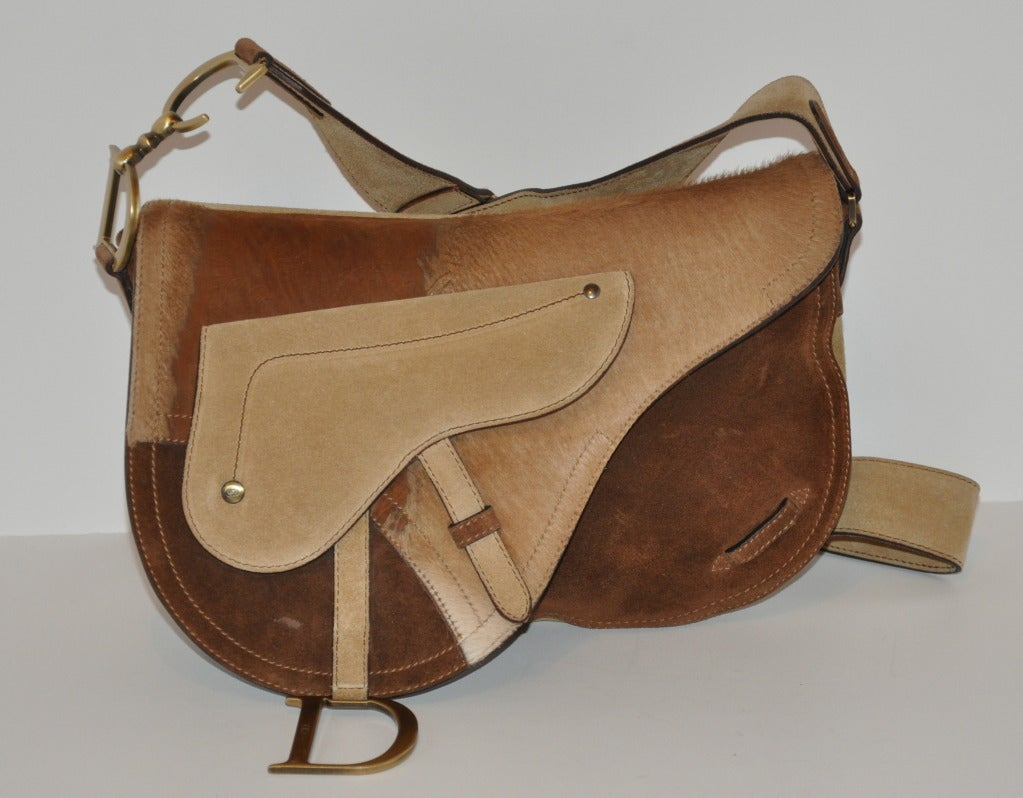 "Christian Dior's ""Limited Edition"" large ""Saddle"" style shoulder bag is of soft calfskin brushed suede. The large front flap is a combination of stenciled leather, pony-like appearance and suede in colors of browns and tans, with adjustable shoulder"