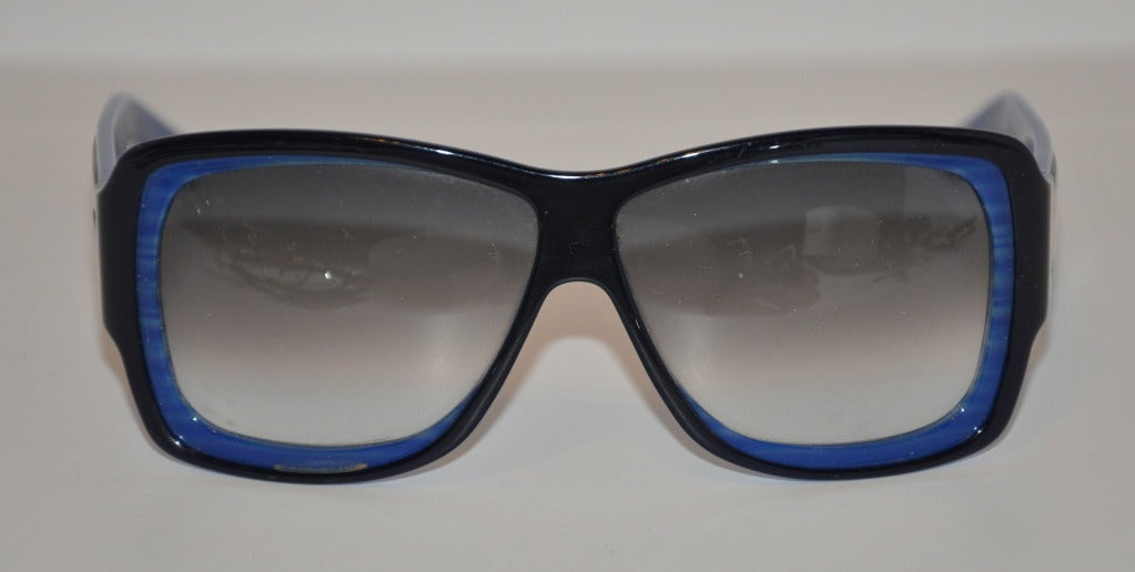 "Yves Saint Laurent wonderful sunglasses are in streaks of French blue and highlighted with black accents. The sides have silver name plate with ""Yves Saint Laurent"". Highly hand-polished with polished black accents on front.
