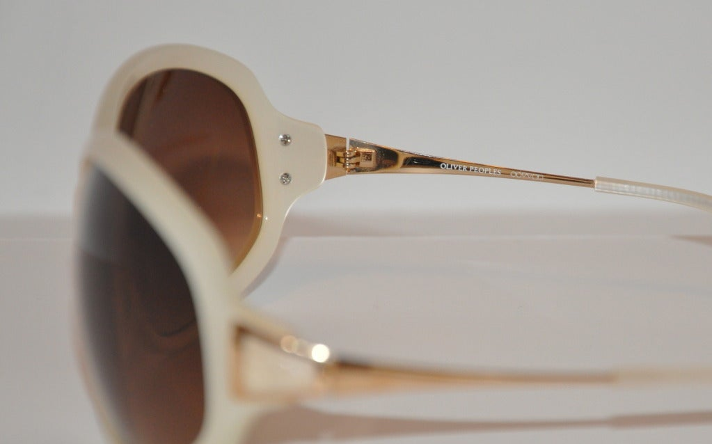Oliver Peoples pearl finish along with gold hardware accents sunglasses measures 2 1/4