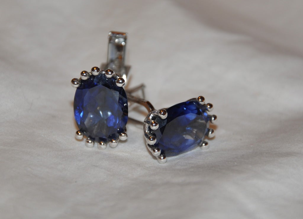 Impressive oval-shaped crystal-clear blue stones surrounded with polished silver tone hardware finishing. Cufflink measures 7/8