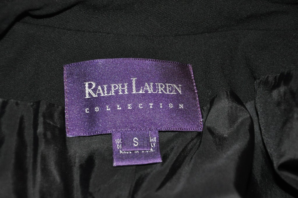 """Ralph Lauren's Black trench coat is fully lined with silk. The trench coat itself is of wool. Classically styled with five(5) front buttons and two large set-in pockets. The back center is styled with a pleated-flat 14 1/2"""" slit.    Underarm"""