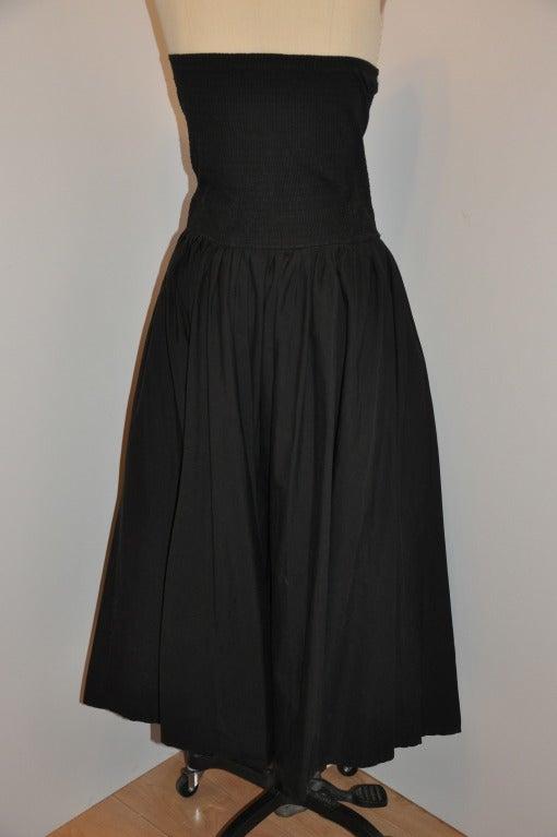 "Norma Kamali black strapless dress has elastic backside for added fit. Full skirt measures 288"" in circumference. Waist-to-hem measures 30 1/4"". Waist measures 31""."