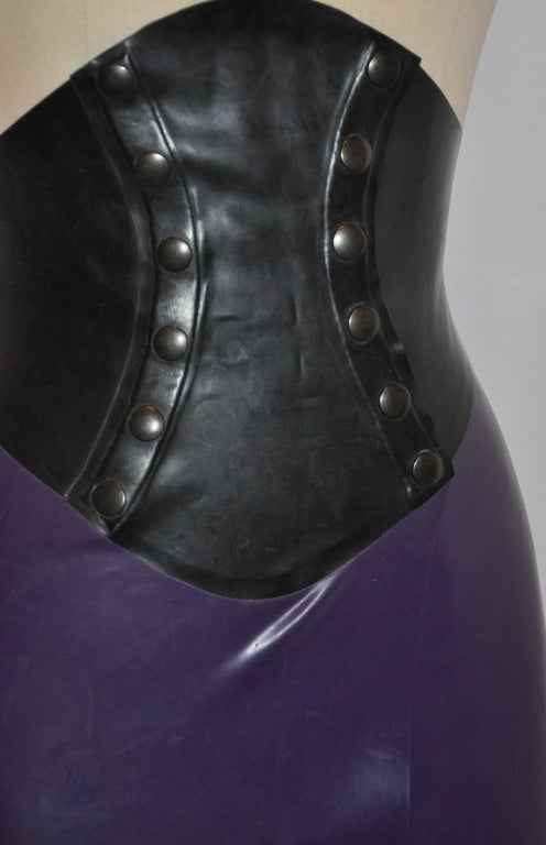"This wicked deep plum & black form-fitting skirt has a double row of heavy-duty metal snaps to hold anyone in! Super form-fitting and shapely, the center length measures 44"", side length measures 41"", waist measures 24"", and the hips are 34""."