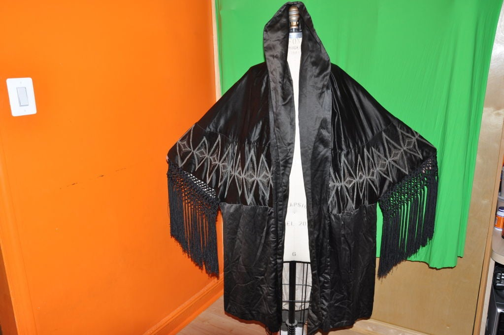 This spectacular Victorian black silk opera coat has hand-knotted fringes on the sleeves. The collar can be worn down, high and even as a hood. On the back center of the neckline, they are soft gathering and there are two darts, one on each back