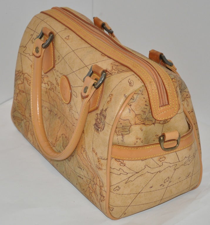 """Allen Edward embossed """"map"""" barrel handbag is accented with beige calfskin leather along with detailed top-stitching and double handles on top. Interior is fully lined and has a interior zippered compartment.    Length measures 10 1/2"""", height of"""