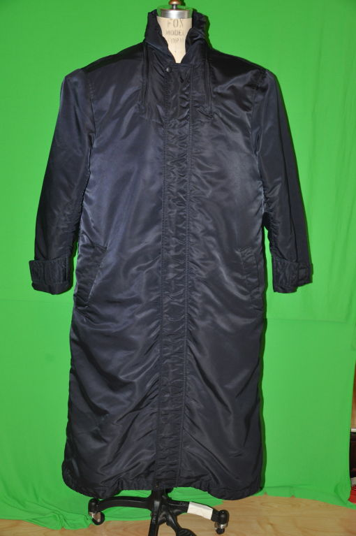 Issey Miyake men's trenchcoat has a hidden hooded tucked along the zippered neck, which extends toward the chest front. There are two interior zipper pockets plus, two huge patch pockets also located in the interior. The exterior front has two
