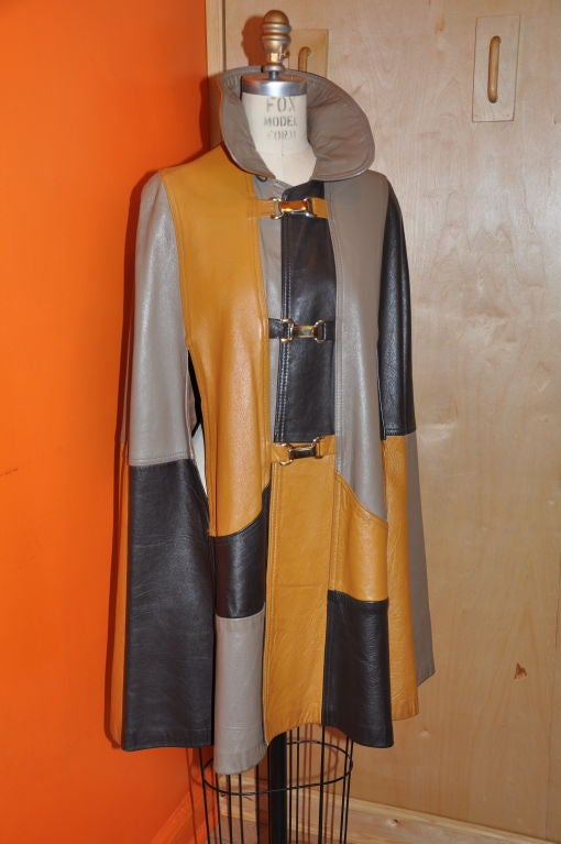 """The multiple colors of this leather patch cape is so '70s. This would be so cool to wear the next time you're going to """"Strawberry Fields""""!!!. On the front of the cape are three large gold-tone snap release closings, with two front pockets and large"""