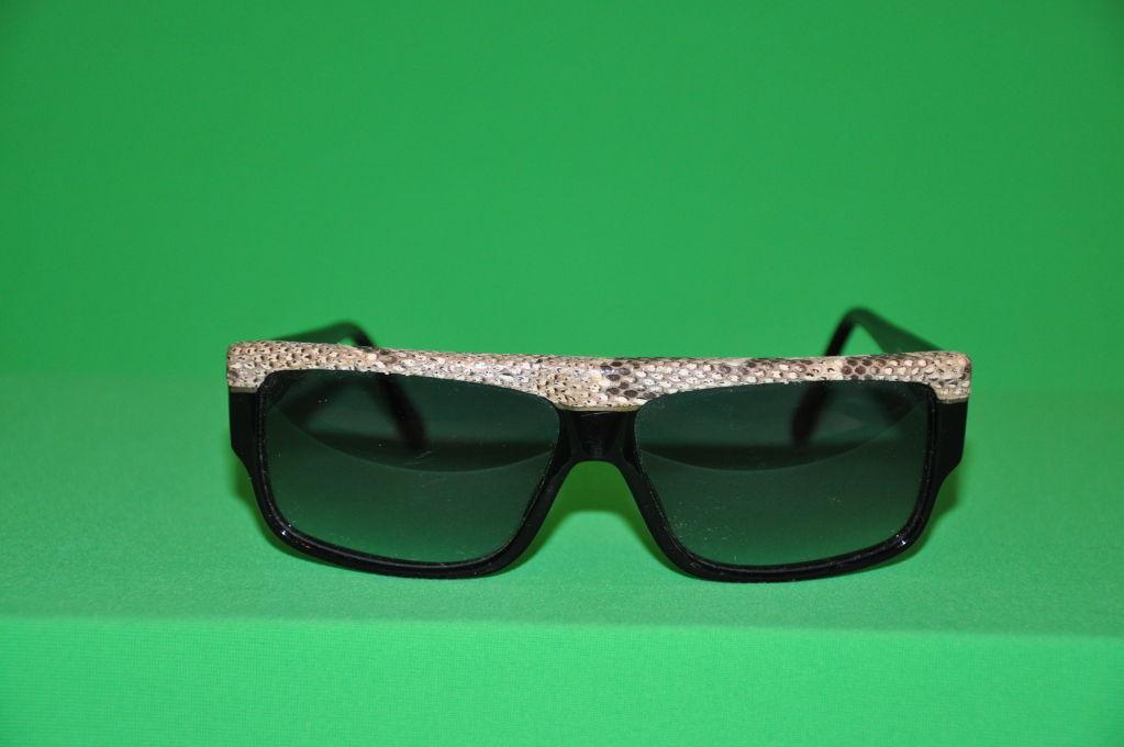 fe4e8e354cc Emmanuelle Khanh black sunglasses has tan and black snakeskin detailing on  front top. The sides
