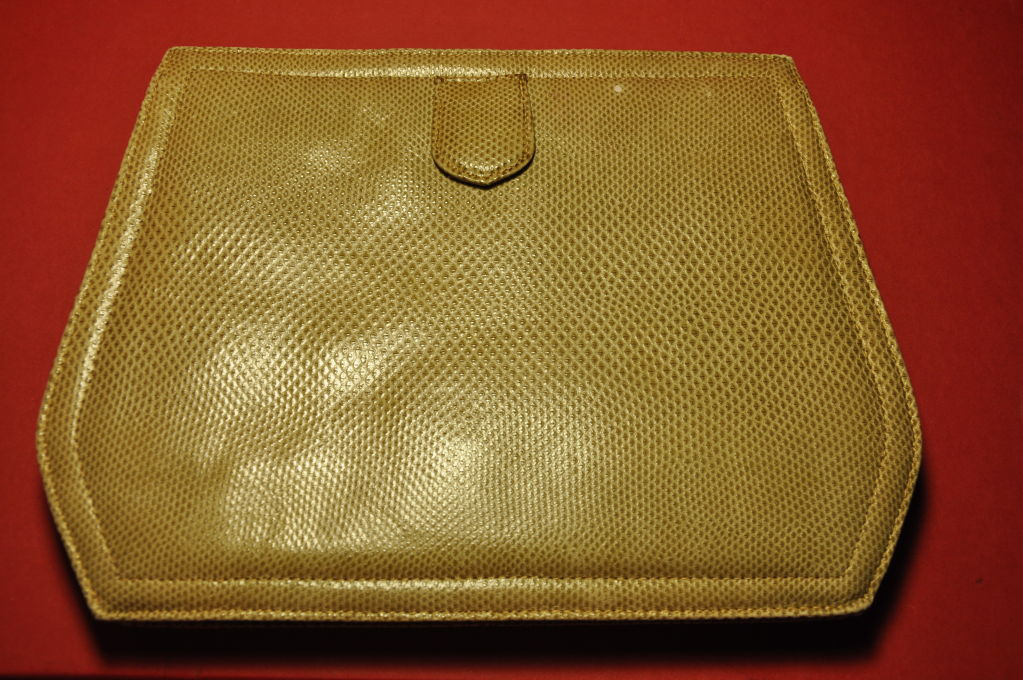 This Jay Herbert Lizard clutch is taupe in color with gold-metal-tone chain shoulder straps. The bag measures 10 1/2