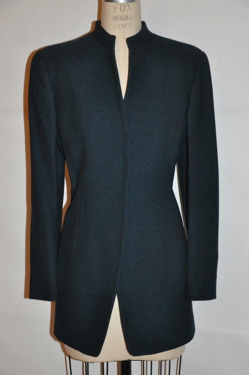 """Giorgio Armani """"Le Collezioni"""" forest green and black textured weave jacket has a manderin collar which measures 1 1/4"""" in height. There are five (5) hidden buttons in front.The center back measures 30"""", front is 28"""", neck-to-shoulder is 5"""","""