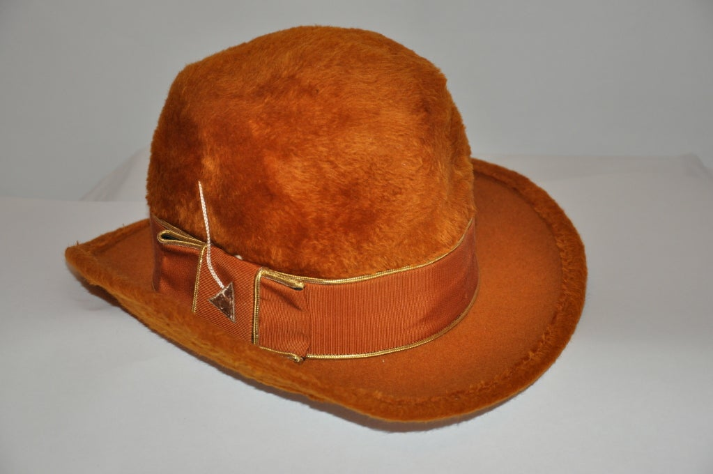 """Mr. John felted hat is in a warm-golden brown hue. The body is crafted in Italy. There's a ribbon and embroidered """"arrow"""" detailing bordered with metallic gold threading. The circumference measures 21"""", height is 5"""", rim is 2"""" wide."""