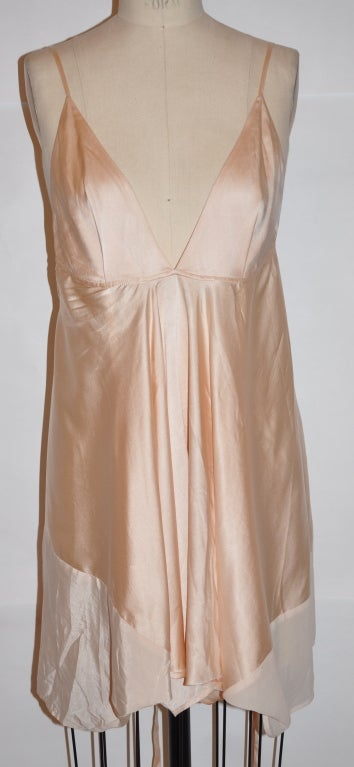 This asymmetrical cut Ann Demeulemeester slip dress is made of rose-colored silk with matching rose-colored silk chiffon detailing. the back center has a silk tie with option to use. Under the right-side underarm is a side slit with hook and eye.